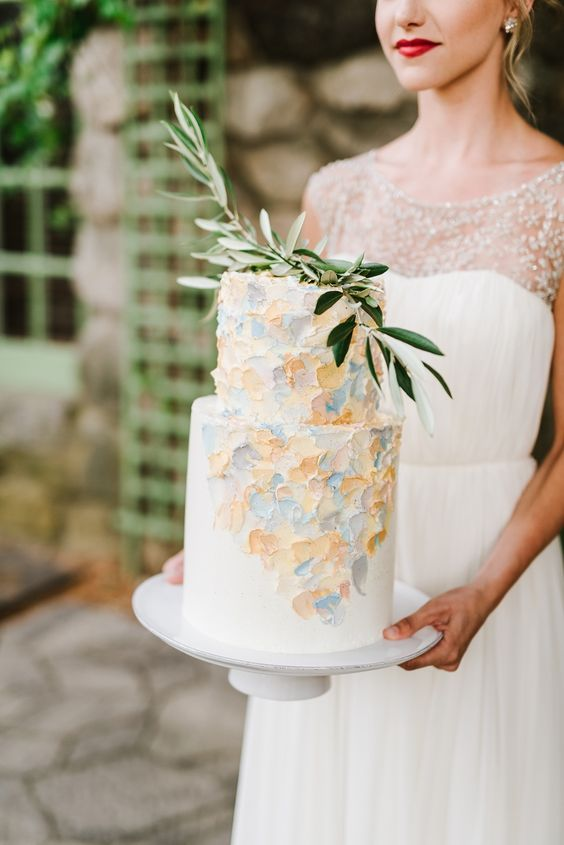 a pretty white wedding cake with pastel brushstrokes and a greenery brunch on top is a very romantic idea