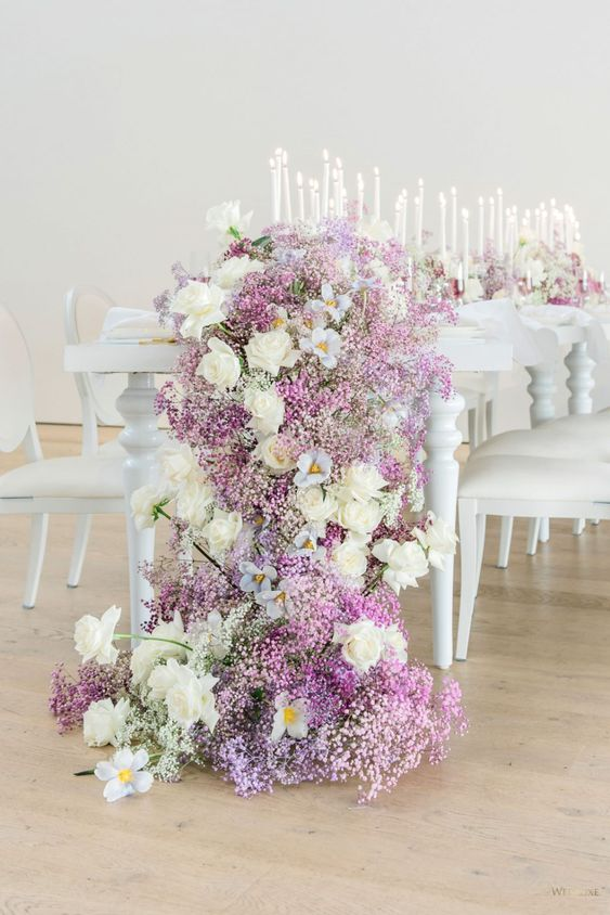 a refined wedding tablescape with white roses and lilac and purple baby's breath, multiple candles and chic white furniture