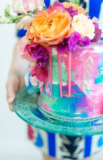 a super colorful wedding cake with pink drip and bold blooms on top is a very lovely and cool idea for a colorful wedding