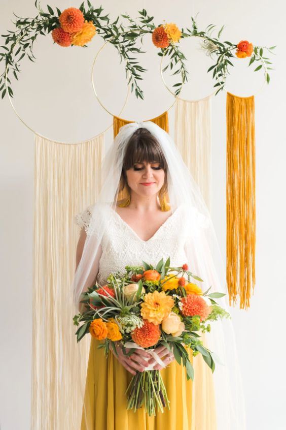 an embroidery hoop with long fringe and greenery and bright blooms is ideal for 70s weddings