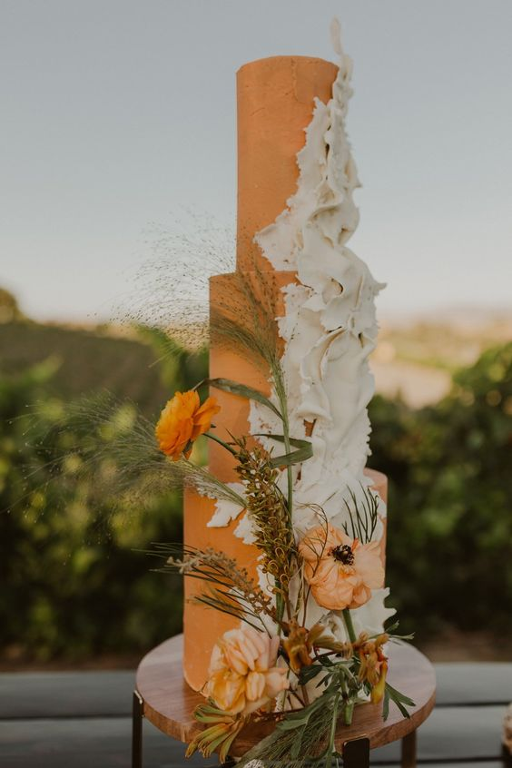 an orange wedding cake with white sugar ruffles, orange blooms and dried herbs plus greenery is chic