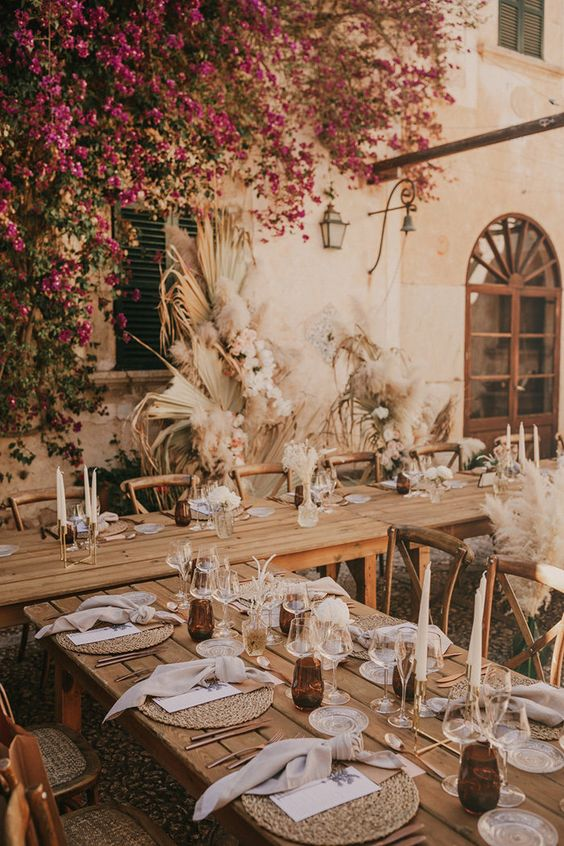 a beautiful boho wedding reception space with dried fronds, neutral blooms and grasses, candles and bold flowers hanging over it