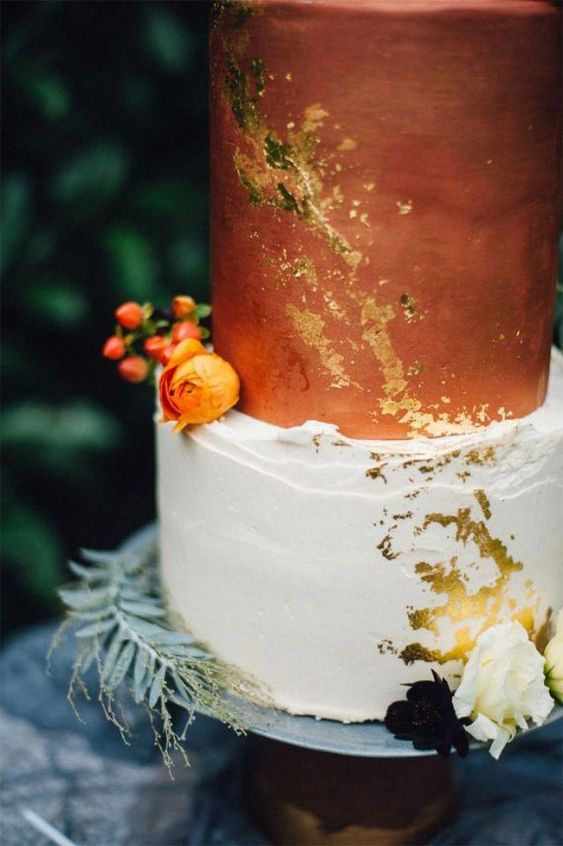 a bold wedding cake with white and a rust tier, gold leaf, bright and neutral blooms and fresh greenery is modern and bold