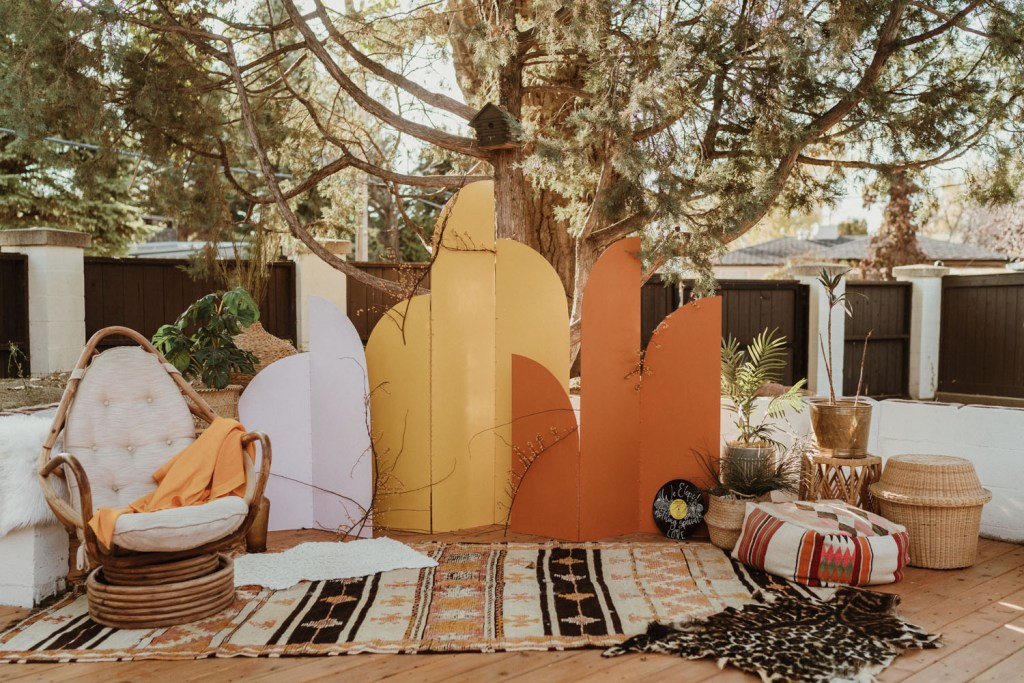 a color block wedding backdrop, potted plants, layered rugs, pillows and baskets for a 70s boho wedding