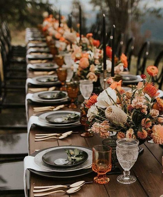 a fantastic modern wedding table setting with rust and orange florals, rust glasses, black plates and candles looks fashion-forward