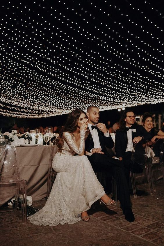 a refined and chic wedding reception done in neutrals, with white blooms, candles and a gorgeous light canopy over the space