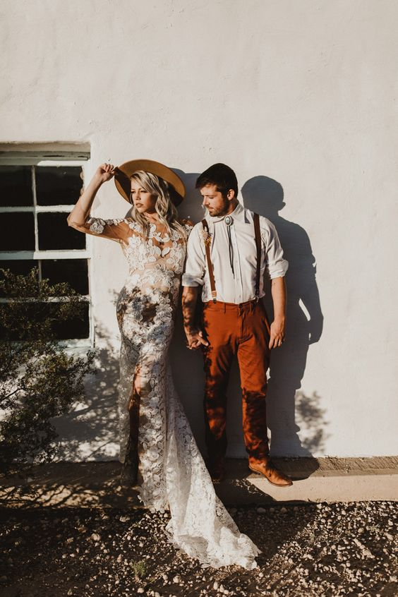 a relaxed boho groom's look with a white shirt, rust pants and matching suspenders, a bolo tie and brown shoes