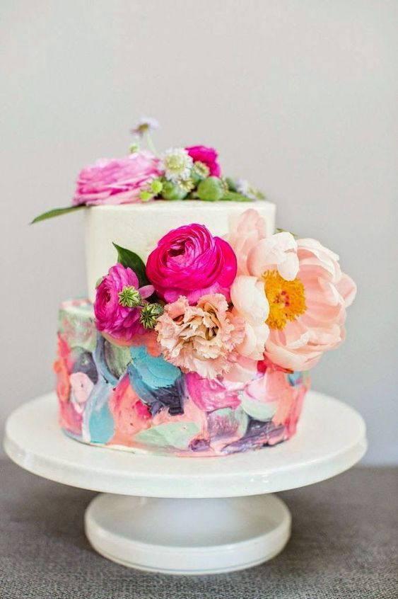 a trendy wedding cake with a bold dimensional brushstroke tier and a white one plus bright blooms here and there