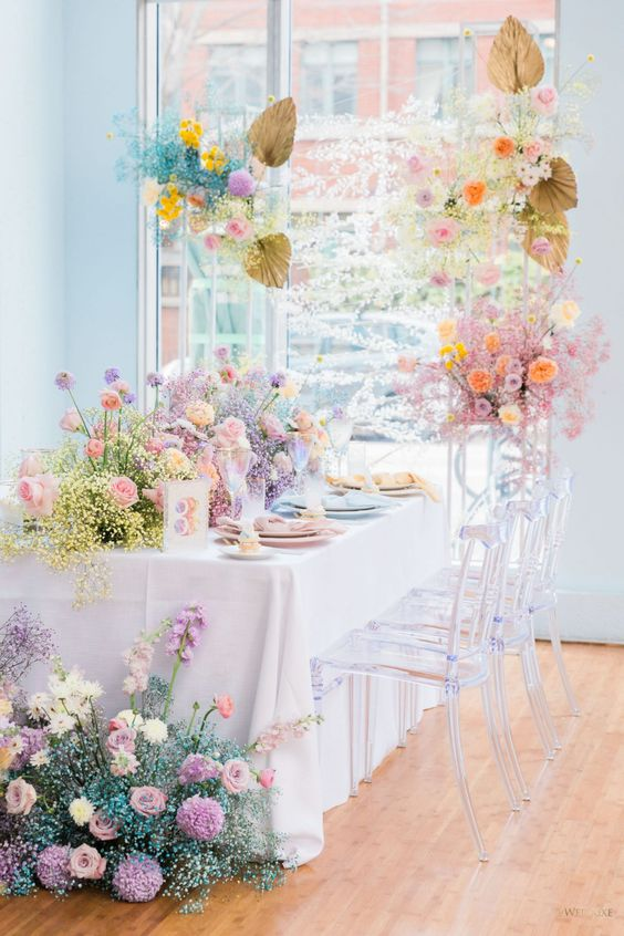 a beautiful rainbow-colored baby's breath and floral wedding reception with gilded palm leaves is a very pretty idea