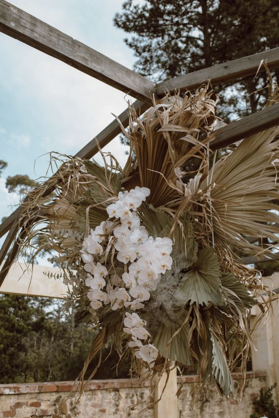 a boho wedding decoration of dried fronds, green fronds and white orchids is amazing for a tropical wedding