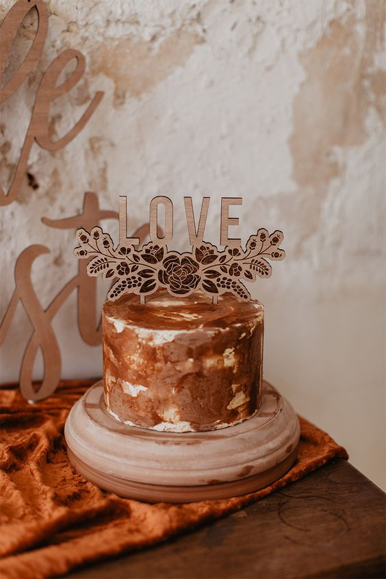 a creative rust and copper brushstroke wedding cake with a plywood lasercut topper is a chic idea for a fall wedding