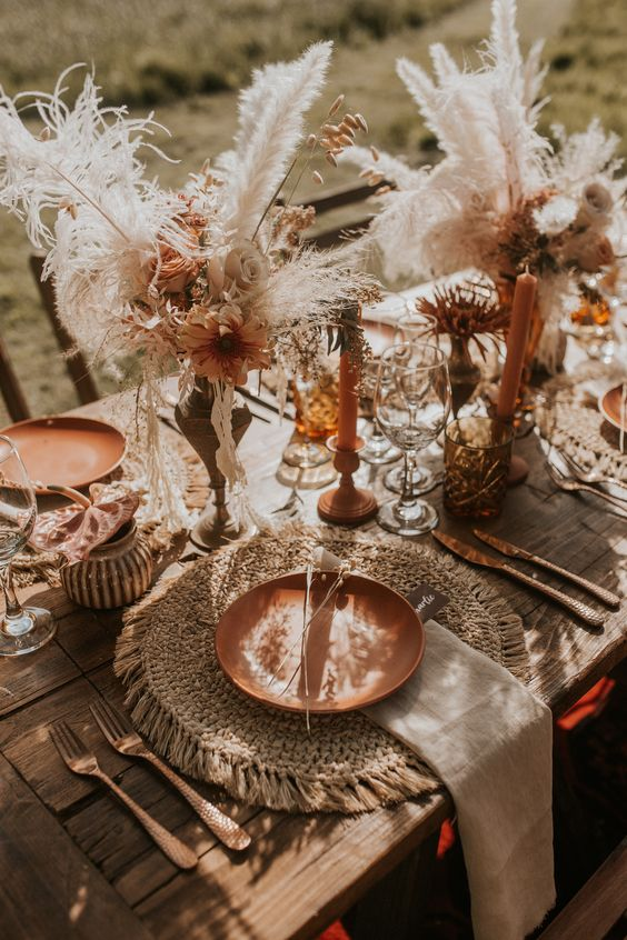 a gorgeous boho wedding tablescape with macrame placemats, rust plates, candles and florals, pampas grass and amber glasses