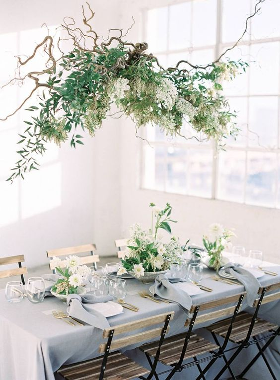 a lovely driftwood hanging installation with greenery and white blooms plus matching centerpieces on the table