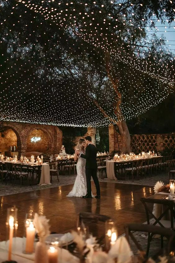 a romantic outdoor ranch wedding reception with a large light canopy and additional candles that create an ambience