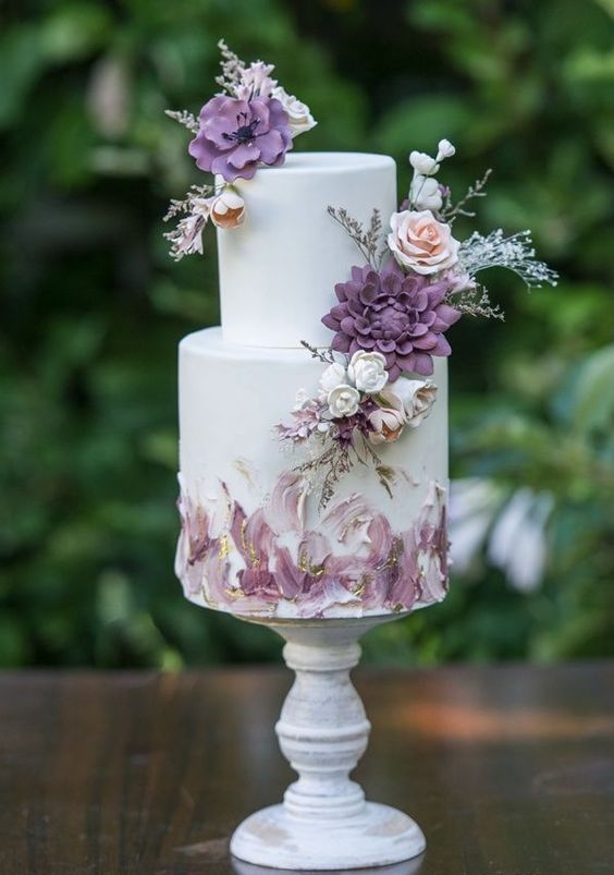 a sophisticated white wedding cake with lavender and purple brushstrokes, gold touches and sugar blooms