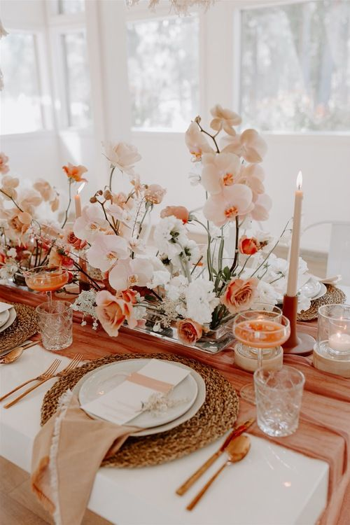 a gorgeous monochromatic wedding tablescape with blush, white and rust blooms, blush napkins and a rust runner, white candles