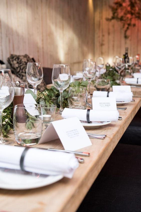a pretty rustic Scandinavian tablescape with a greenery runner, white napkins and stationery and candles plus an uncovered table