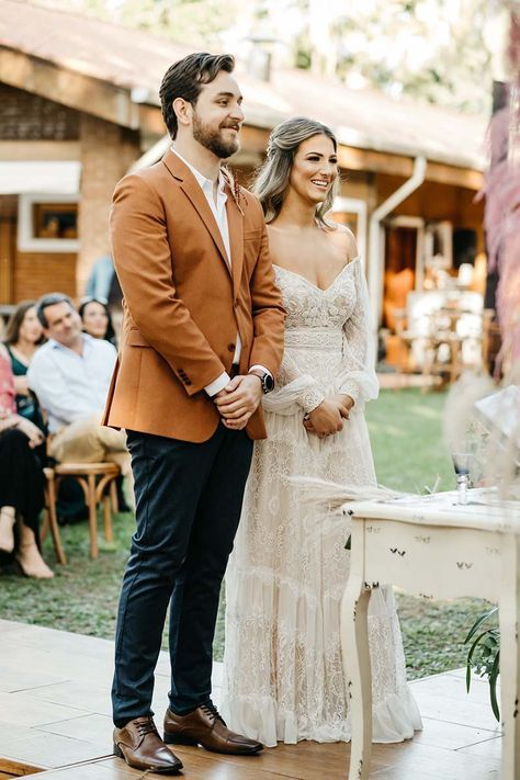 a simple and stylish look with a white shirt, a rust-colored blazer, navy pants, brown shoes and a watch for a boho wedding