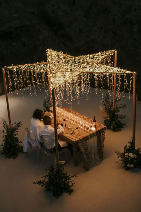a star-shaped canopy of lights with some hanging lights is a pretty idea for a micro wedding or an elopement