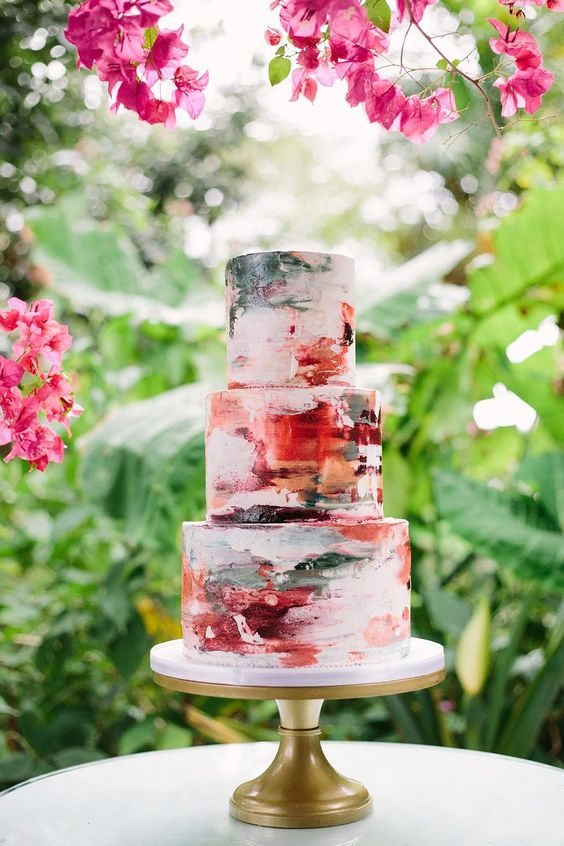 a super bold brushstroke wedding cake in green, burgundy, red and orange for a colorful summer wedding