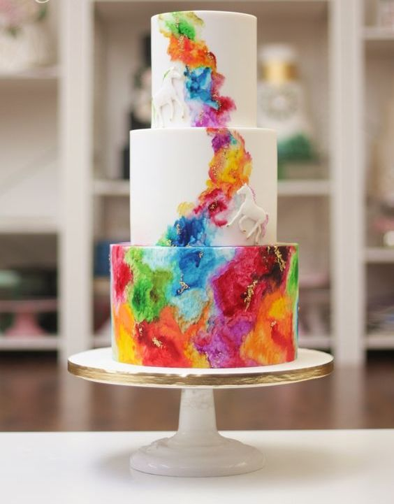 a white wedding cake with bold watercolors, sugar horses and gold leaf is a stylish and bold idea for a colorful wedding