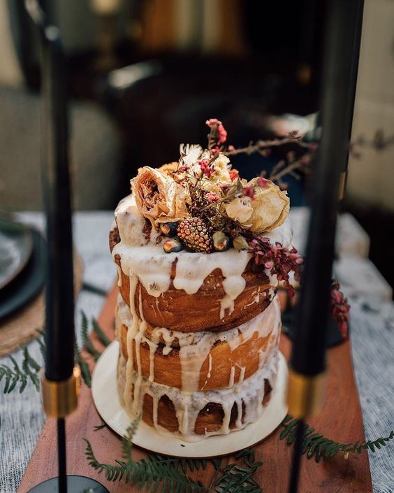an amazing boho cinnamon roll wedding cake of three tiers, white icing, dried blooms and gilded berries on top