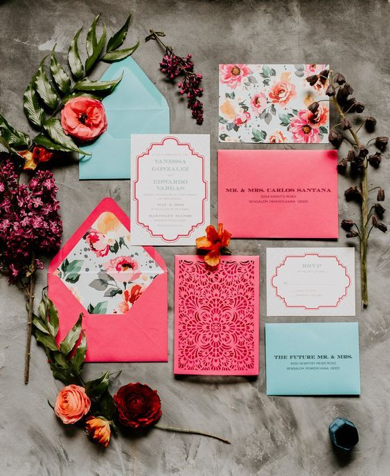 a bright floral invitation suite with pink and mint envelopes, bold floral lining and a laser cut piece