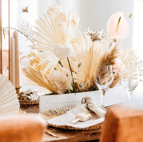 a centerpiece of dried fronds, tropical blooms, pampas grass and some dried herbs and blooms for a boho desert wedding
