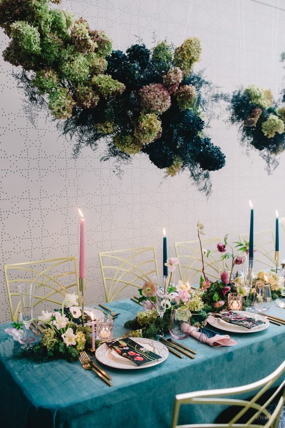 a lush green and navy floral and herb installation plus colorful floral centerpieces and navy and pink candles is chic
