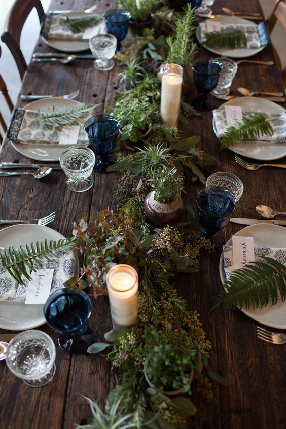 a pretty woodland Scandinavian wedding tablescape with a greenery runner, candles, blue glasses, fern leaves and printed linens