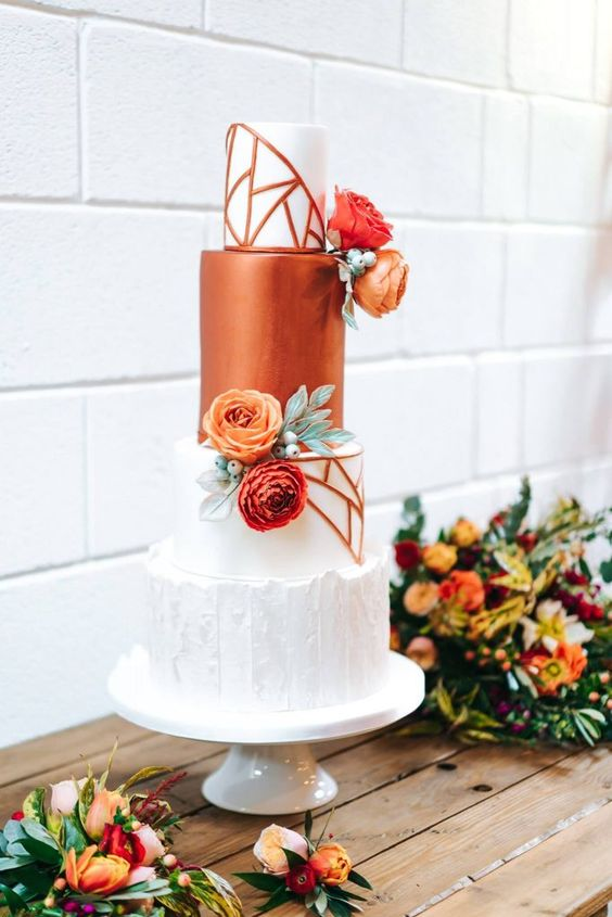 a refined modern wedding cake with a white textural tier, white geometric tiers, a sleek copper tier and bright blooms