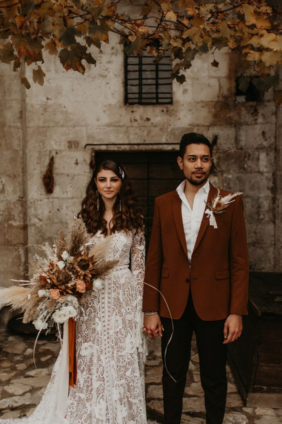 a white shirt, a rust-colored blazer and black trousers and a dried flower boutonniere for a chic fall wedding
