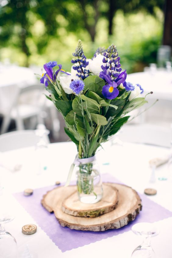 32 a beautiful and simple wedding centerpiece of a jar with white and purple blooms and greenery placed on stacked wood slices