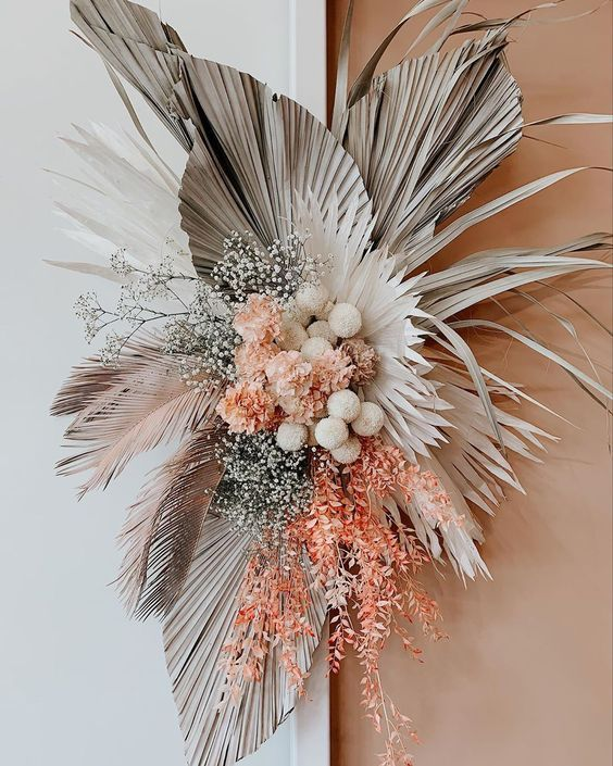 a chic wedding decoration of dried fronds, orange and white blooms, baby's breath and some bright foliage is very cool and bright