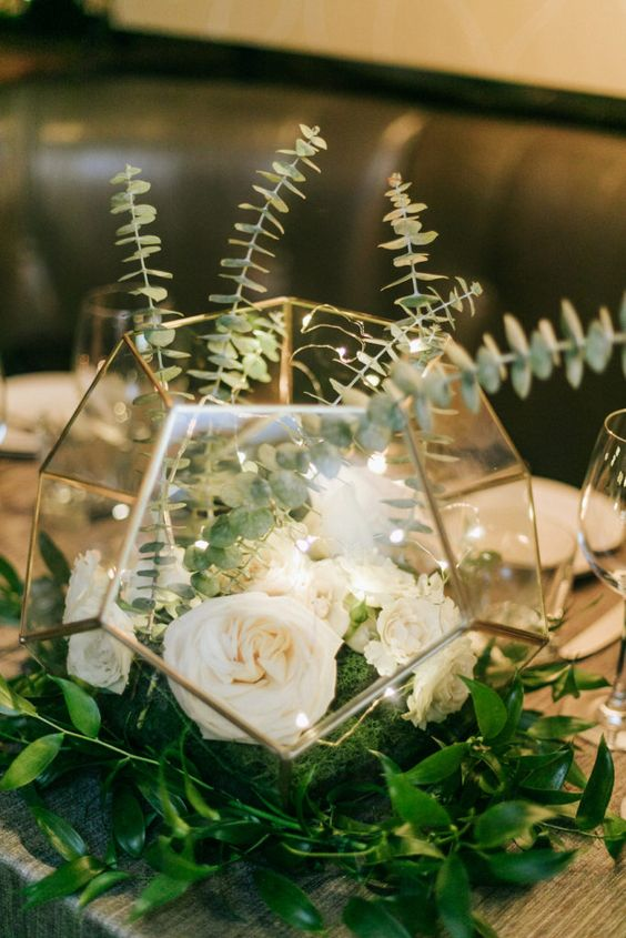 a faceted terrarium with neutral blooms, greenery and lights is a very pretty and chic centerpiece for a wedding