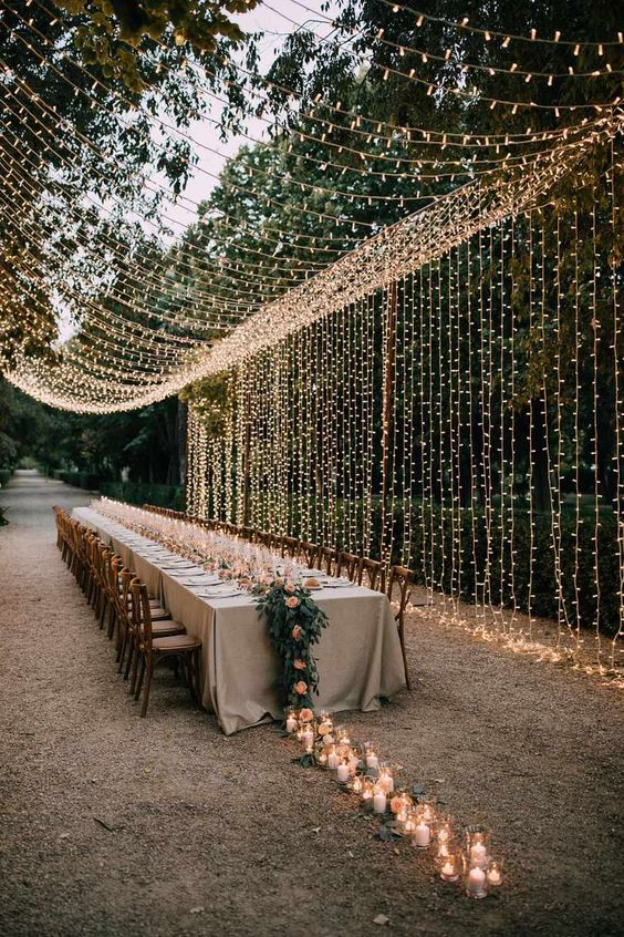 an elegant outdoor wedding reception with a long greenery and bloom runner with candles on the ground and a jaw-dropping light canopy over it
