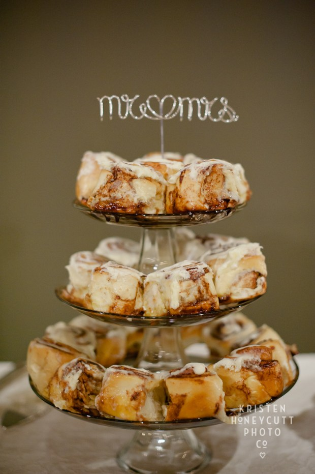 a glass stand with cinnamon buns and a calligraphy topper is a pretty and cool alternative to a wedding cake
