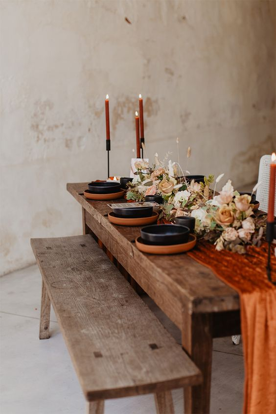 a lovely modern fall wedding tablescape with a rust fabric runner, terracotta chargers, black tableware, rust candles and pastel blooms and greenery