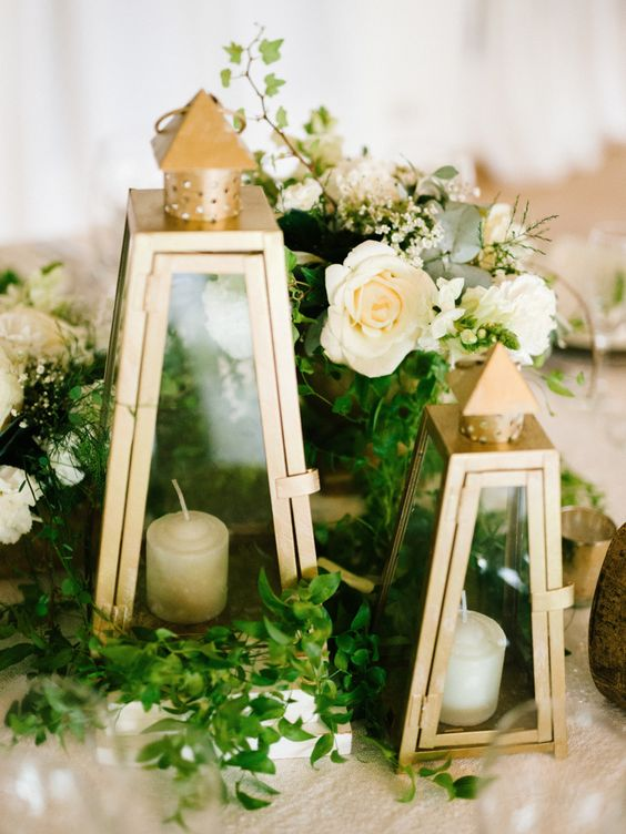 a lovely wedding centerpiece of greenery, neutral blooms and elegant metallic candle lanterns for a refined and romantic wedding
