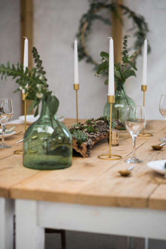 a rustic Scandinavian tablescape with an uncovered table, candles, a piece of driftwood with succulents, green bottles and leaves
