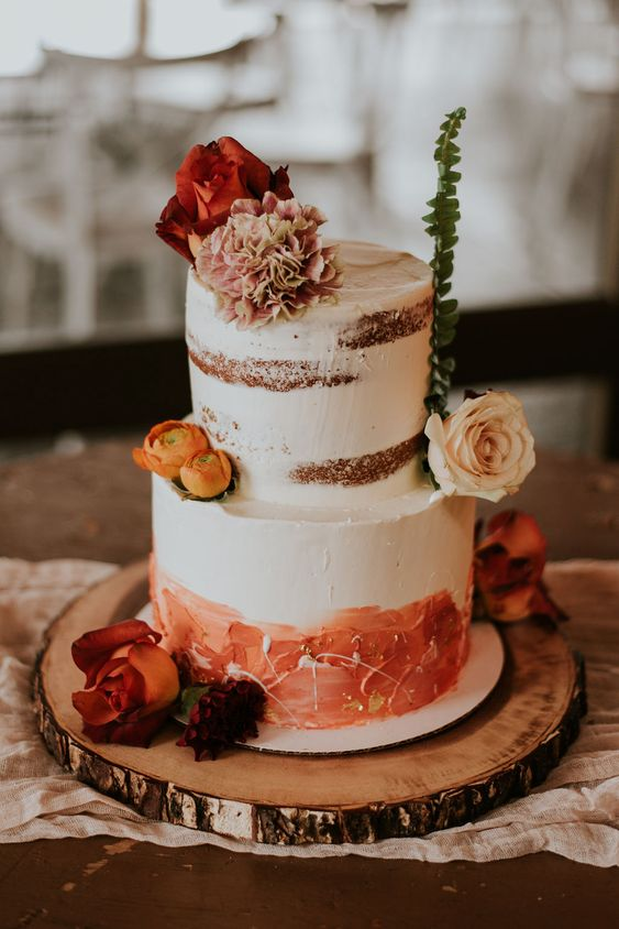 a rustic naked wedding cake with a buttercream tier and rust decor, with fresh blooms and greenery