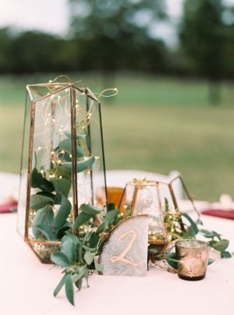 a terrarium with greenery and succulents plus lights and an agate slice table number is a stylish idea