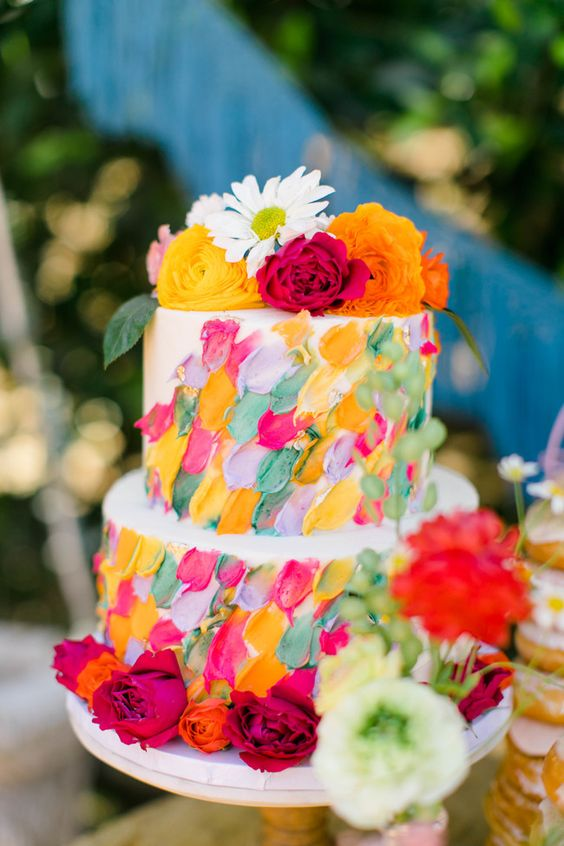 a white wedding cake with super bright textural and dimensional brushstrokes and bold blooms on top and around the cake