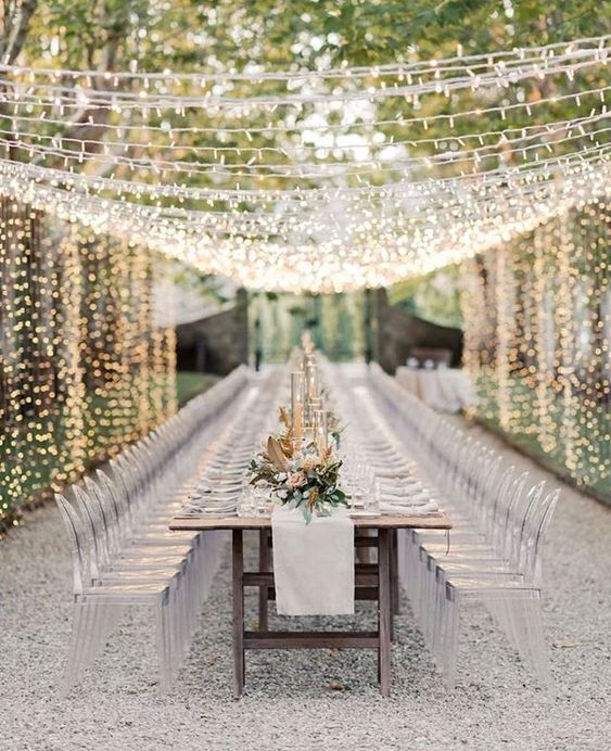 an exquisite modern wedding receotion in neutrals, with acrylic chairs and a light canopy over it is very chic