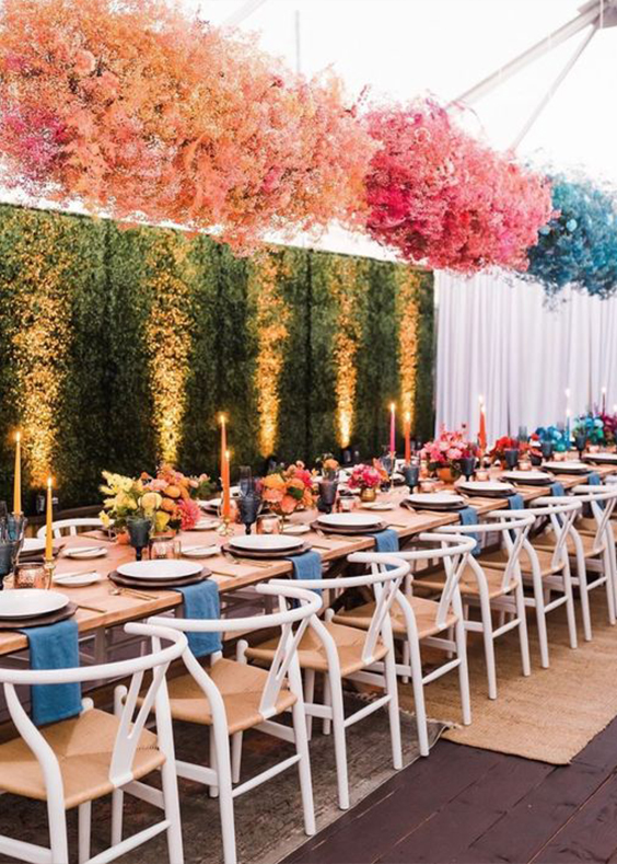 ombre colorful baby's breath installations over the table and colorful blooms and candles for much fun