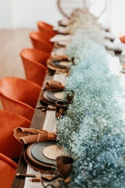 a blue baby's breath table runner, dark glasses and brown napkins for a contrasting and bold wedding tablescape