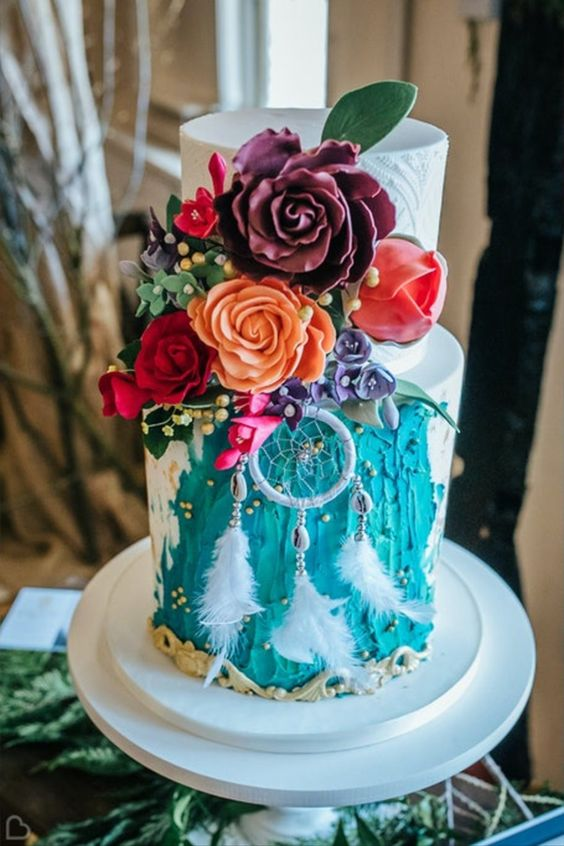 a bold white and turquoise wedding cake with beads, bright sugar blooms and leaves, lace detailing and a dreamcatcher with feathers