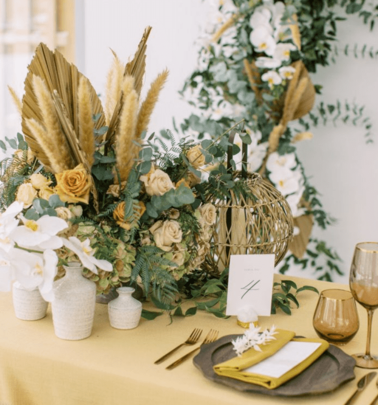 a fantastic wedding centerpiece of green hydrangeas, blush and orange roses, eucalyptus, pampas grass and dried fronds is super cool
