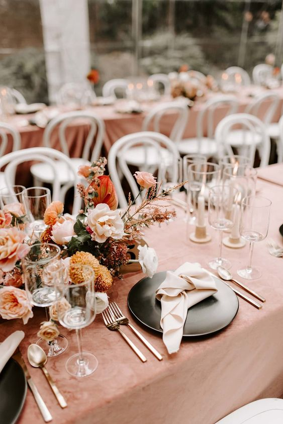 a lovely sunset-toned wedding tablescape with a rust tablecloth, rust, orange, blush and white blooms and candles is all chic