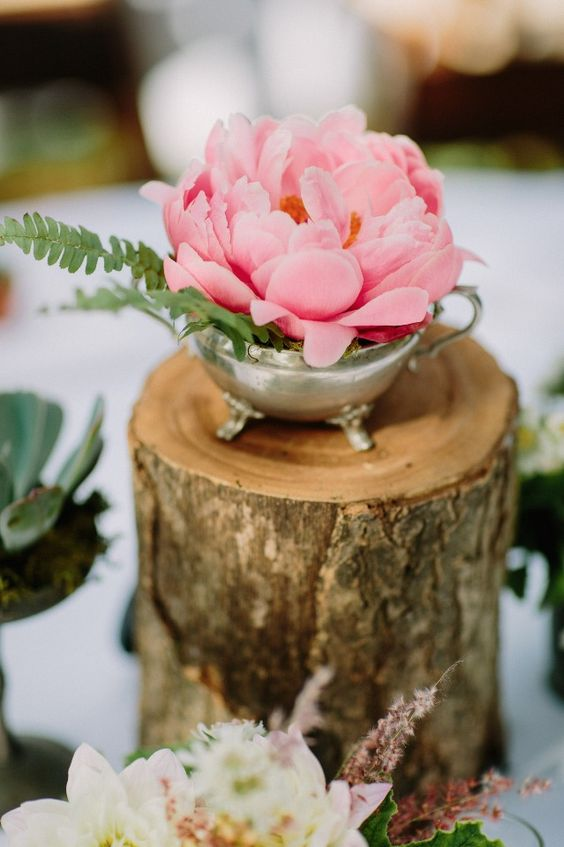 34 a pretty and bright  wedding centerpiece of a silver sugar pot, a large pink bloom and fern leaves on a tree stump